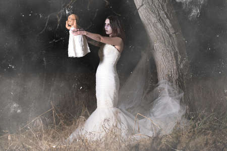 Horror Scene of a Woman Possessed holding a doll.