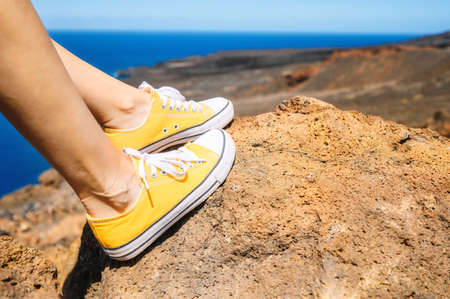 Woman Relaxed, Enjoying Landscape. Traveler Sitting On Rock wearing yellow sneakers. Summer Vacation. Close up. Stock Photo