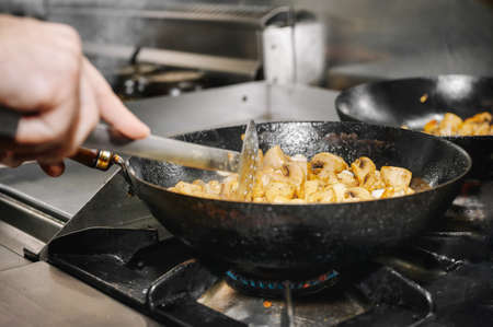 Chef cooking mushrooms in frying pan on burning fire.