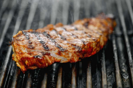 Close up of delicious beef steak on flaming grill.