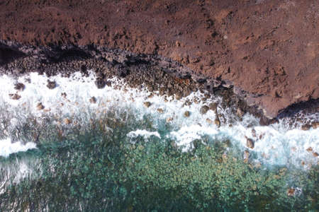 Aerial top view of waves splashing on rocky volcanic coastline. High quality photo.