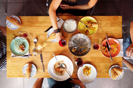 Aerial view of a group of friends dinning together. Directly above photography of unrecognizable people eating at restaurant.