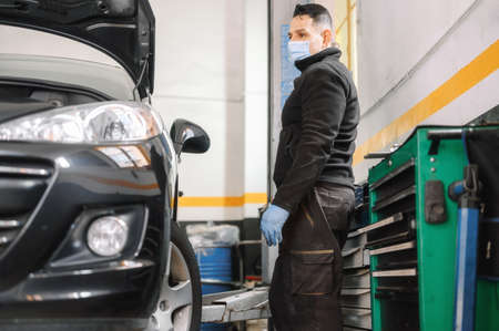 Professional mechanic with protective face mask, repairing a car in service garage. 스톡 콘텐츠