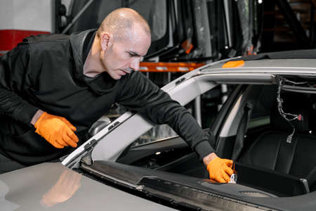 Close up, Car glazing, fixing and repairing a windshield. Windscreen replace process of a car at a garage service. Cleaning a dashboard. 스톡 콘텐츠