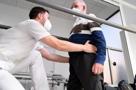 Physiotherapist helping senior patient walk between parallel bars. Zdjęcie Seryjne