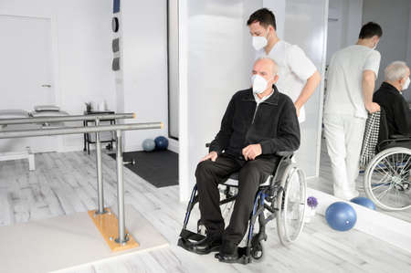 Male Nurse assisting a senior handicapped patient in wheelchair at rehabilitation center. Zdjęcie Seryjne