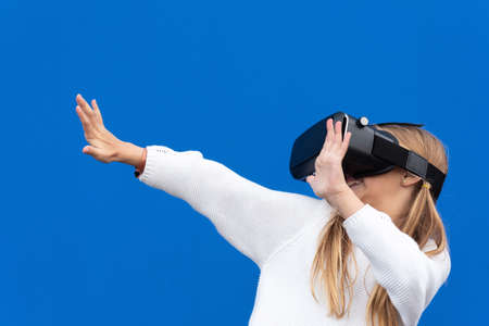 Young girl with virtual reality glasses. Isolated on blue background. VR headset.