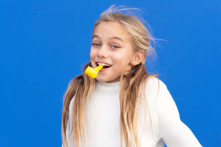 Studio portrait of a happy, smiling young girl celebrating birthday party, holding party blower in mouth having fun, isolated on blue.