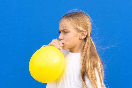 Close up photo of nice pretty lovely girl inflate ballon have free time positive cheerful funny girl isolated on blue colorful background Reklamní fotografie
