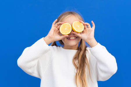 Overjoyed blond haired girl in white sweater smiling while covering eyes with bright lemon slices isolated on blue background Reklamní fotografie