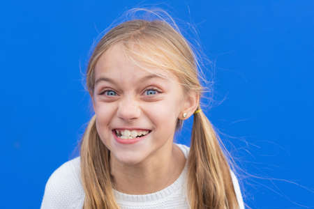 Cute young girl making funny face over blue background. Copy space.