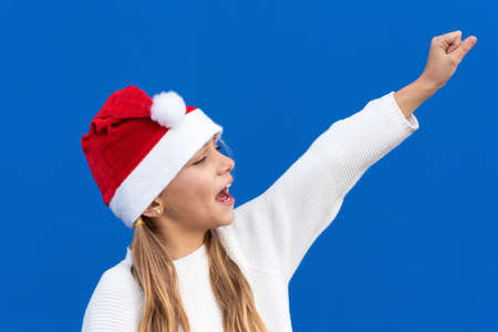 Joyful Young girl in Santa hat gesturing on blue background.
