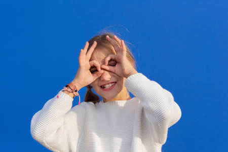 Funny girl making eyeglasses from hands, isolated on blue background.