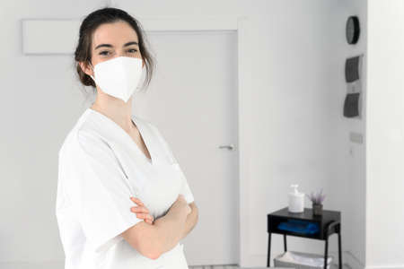 Friendly female physiotherapist posing in modern clinic wearing protective face mask during pandemic