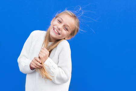 Overjoyed girl holding pigtails and laughing