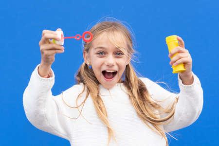 Funny girl blowing soap bubbles Фото со стока