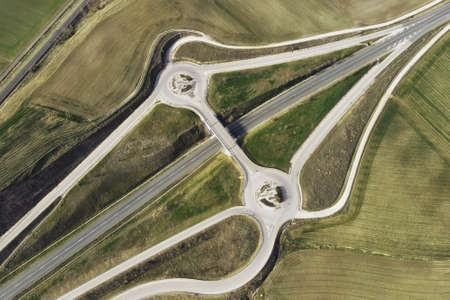Aerial drone view over a country road junction intersection. Traffic on flyover at rural scenery