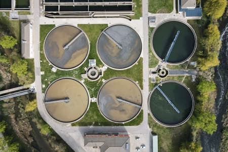 Aerial top view of round polls in wastewater treatment plant, filtration of dirty or sewage water.