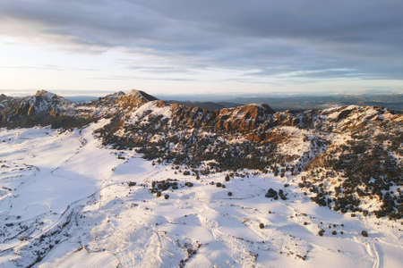 Aerial view of snow covered mountains at sunset in Obarenes mountain range, Burgos province, Spain.