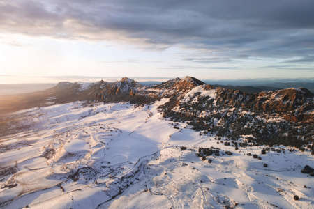 Aerial view of snow covered mountains at sunset