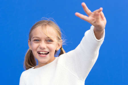 Young beautiful blond girl wearing casual sweater over blue background smiling looking to the camera showing fingers doing victory sign. number two. Фото со стока