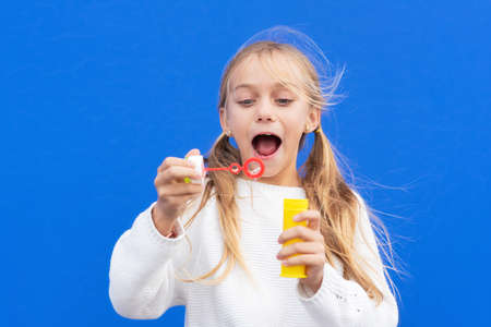 Funny girl blowing soap bubbles Stock Photo