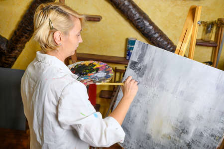 Happy woman paints on canvas using thin brush. Canvas stands on the easel. Artist draws at easel. Side view of female painting picture on canvas in art home studio Zdjęcie Seryjne