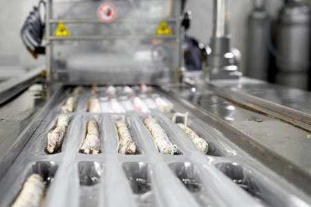 Sausages. Packing line of sausages Fuet is a Catalan thin, cured, dry sausage of pork meat in a pork gut. Industrial manufacture of sausage products.