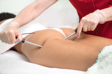 Woman having cosmetic galvanic beauty treatment in spa. Therapist applying low frequency current