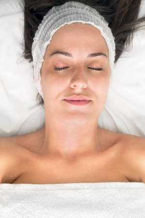 Young woman laying eyes closed, getting facial beauty treatment, view from above. Zdjęcie Seryjne