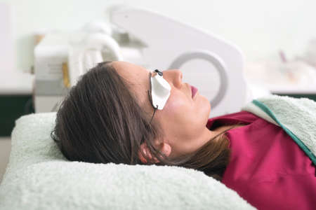 woman lying with protection glasses in beauty salon. Zdjęcie Seryjne