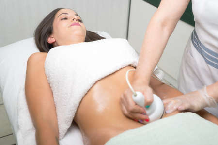 Ultrasound cavitation body contouring treatment. Woman getting anti-cellulite and anti-fat therapy in beauty salon. Zdjęcie Seryjne