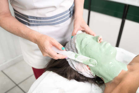 Close up of woman enjoying cosmetic mask for face in professional beauty salon. Relaxing treatment in medicine and spa concepts.