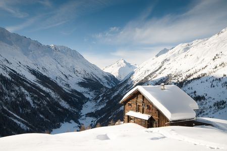 lodges: winterscene of alpine valley with snow coverd cabin