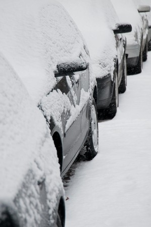 Bunch of snow covered cars  standing in a row