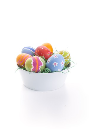 An isolated white bowl with a bunch of rough painted easter eggs