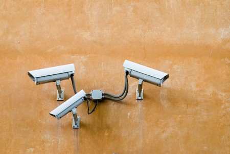 Three surveillance cameras on terracotta wall