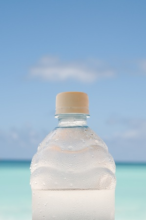 Cold bottle of water covered with drops