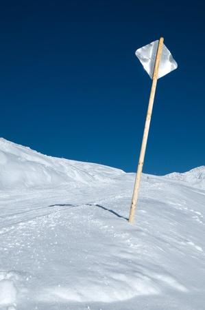 Back side of a metal sign at ski slope in front of blue sky