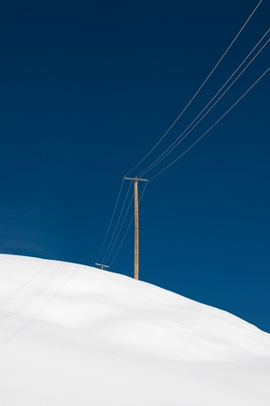 Lone power pole in front of blue sky Stock Photo