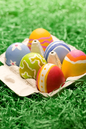 A small box of easter eggs on artificial gras