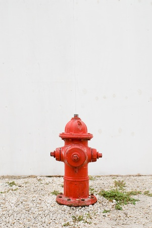 red hydrant in front of plain white fence
