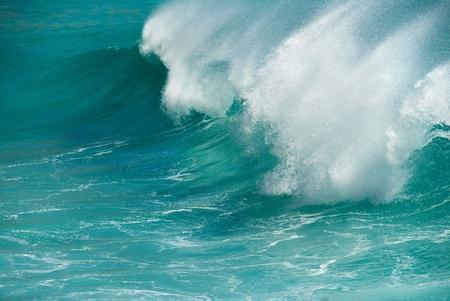 A powerful turquoise ocean wave breaking on shore photo