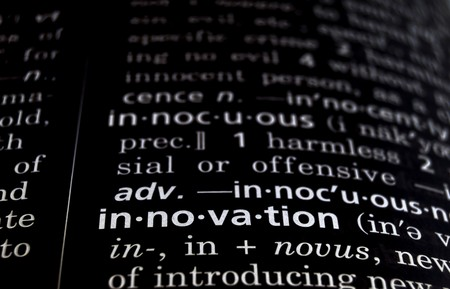 defined: The word innovation in a dictionary, white on black Stock Photo
