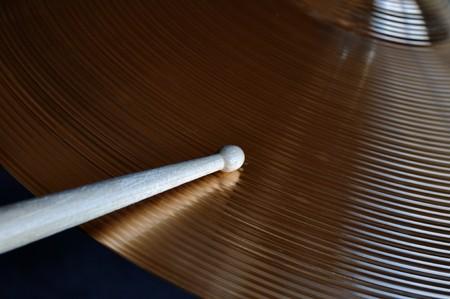 cymbal: Close-up of a drumstick striking a shiny cymbal Stock Photo