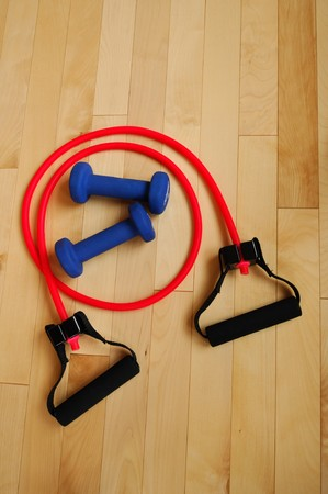 stretchy: Red Resistance Band and Blue Weights on Hardword Fitness Center Floor, view from above