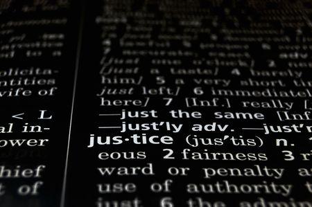 defined: La parola giustizia in un dizionario, bianco su fondo nero