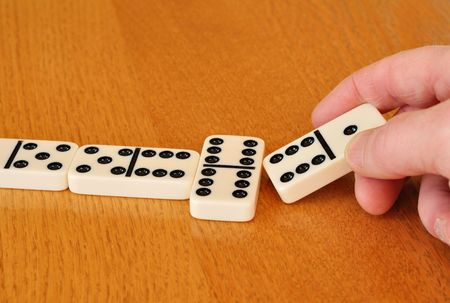 Playing Dominoes on a wood table