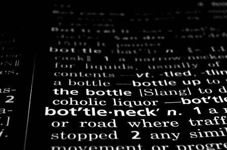 The word bottleneck in a dictionary, white on black photo