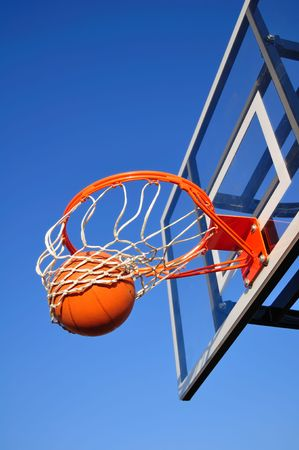 Basketball Shot Falling Through the Net, Blue Sky, vertical, copy space photo